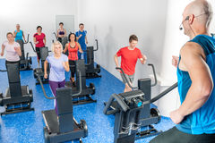 Class of young adults with fitness trainer. Alpinning class of young adults with fitness personal trainer Royalty Free Stock Photos