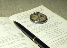 Classbook, penna och gamla klockor Royaltyfria Bilder