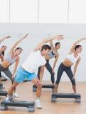 Classe che fa allungando esercizio nello studio di forma fisica Immagine Stock