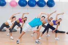 Classe che fa allungando esercizio nello studio di forma fisica Immagini Stock Libere da Diritti
