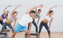Classe che fa allungando esercizio nello studio di forma fisica Fotografie Stock