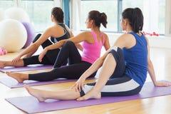 Classe che fa la mezza posa spinale di torsione sulle stuoie alla classe di yoga Fotografia Stock Libera da Diritti