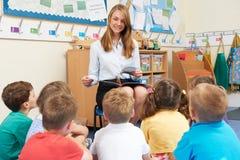 Classe d'école primaire de Reading Book To de professeur Image stock