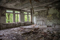 Classe d'école vide avec des débris et des fenêtres cassées Photographie stock libre de droits