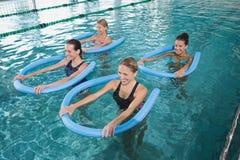 Classe da aptidão que faz a ginástica aeróbica do aqua com rolos da espuma foto de stock