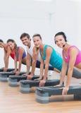 Classe da aptidão que faz o exercício da ginástica aeróbica da etapa Imagens de Stock