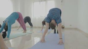 A classe da ioga feita do meio envelheceu mulheres e um homem novo que tenta poses novas e que escuta seu instrutor fêmea - filme