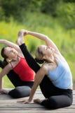 Classe da ioga: Pose da ioga do relógio de sol fotografia de stock