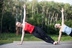Classe da ioga: Pose lateral da prancha fotografia de stock