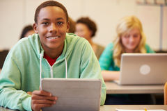 Classe de At Desk In do estudante da High School que usa a tabuleta de Digitas Fotos de Stock