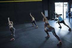 Classe de forme physique dans la flexibilité et l'élasticité d'intérieur de formation de gymnase photos libres de droits