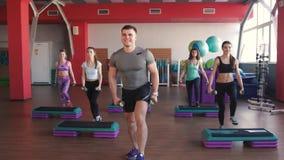 Classe de ginástica aeróbica que pisa e que aplaude junto no gym vídeos de arquivo