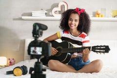 Classe de guitare de Girving de femme sur l'Internet avec le cours visuel photo libre de droits