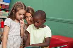 Classe de jardin d'enfants lisant un livre Images libres de droits