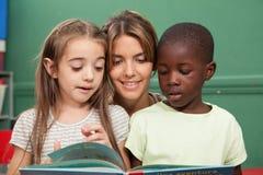 Classe de jardin d'enfants lisant un livre Photographie stock libre de droits