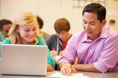 Classe de With Teacher In d'étudiant de lycée utilisant l'ordinateur portable Photographie stock libre de droits