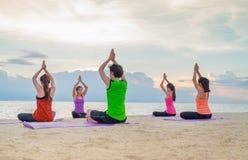 Classe de yoga à la plage de mer dans le coucher du soleil de soirée, groupe de personnes faire photos stock
