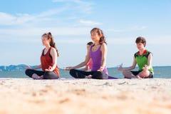 Classe de yoga à la plage de mer dans le jour ensoleillé, groupe de personnes faisant le lotu photographie stock libre de droits