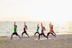 Classe de yoga à la plage de mer dans le temps de coucher du soleil, groupe de personnes faisant Wa images stock