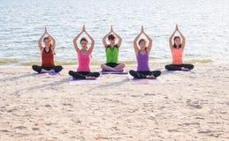 Classe de yoga à la plage de mer dans la soirée, groupe de personnes faisant l'arbre p Images libres de droits