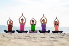 Classe de yoga à la plage de mer dans la soirée, groupe de personnes faisant l'arbre p photographie stock