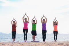 Classe de yoga à la plage de mer dans la soirée, groupe de personnes faisant le namast Image libre de droits