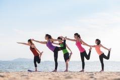Classe de yoga à la plage de mer dans la soirée, groupe de personnes faisant le seigneur o Photo stock