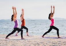 Classe de yoga à la plage de mer dans la soirée, groupe de personnes faisant Warrio Photos libres de droits