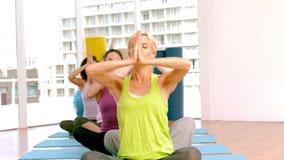 Classe de yoga soulevant leurs mains banque de vidéos