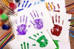 Classe del mestiere e di arte, stampe della mano del bambino e rifornimenti di arte sullo scrittorio della scuola Fotografia Stock