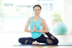 Classe dell'interno della donna di yoga asiatica di addestramento in piccione e nel namaste As Fotografie Stock