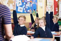 Classe des élèves d'école primaire répondant à la question Photos libres de droits