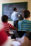 Classe di At Blackboard Giving dell'insegnante Medio Evo di per la matematica Immagini Stock Libere da Diritti
