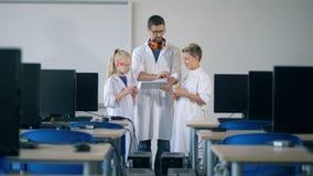 Classe di Digital con due anni dell'adolescenza e un ricercatore con un computer della compressa stock footage