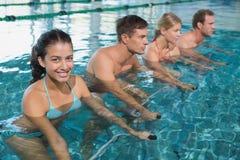 Classe di forma fisica che fa aerobica dell'acqua sulle bici di esercizio fotografia stock libera da diritti
