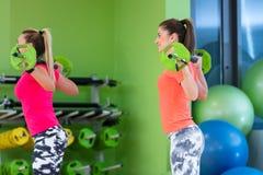 Classe di forma fisica con l'esercitazione della donna Allenamento delle femmine in palestra con il bilanciere Immagine Stock
