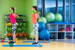 Classe di forma fisica con l'esercitazione della donna Allenamento delle femmine in palestra con il bilanciere Immagini Stock