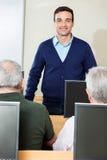 Classe di Standing In Computer dell'istitutore mentre studenti senior allo scrittorio Fotografia Stock