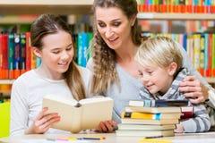 Classe di studenti con il loro insegnante nella biblioteca di scuola Fotografie Stock Libere da Diritti