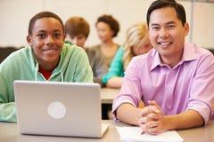 Classe di With Teacher In dello studente della High School facendo uso del computer portatile Fotografia Stock Libera da Diritti