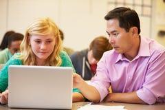 Classe di With Teacher In dello studente della High School facendo uso del computer portatile Immagini Stock Libere da Diritti