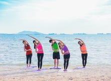 Classe di yoga alla spiaggia del mare nella sera, gruppo di persone che fanno Standi Fotografie Stock