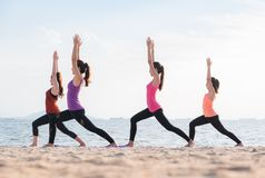 Classe di yoga alla spiaggia del mare nella sera, gruppo di persone che fanno Warrio Fotografie Stock Libere da Diritti