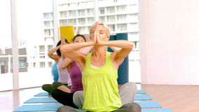 Classe di yoga che solleva le loro mani