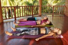 Classe di yoga con le donne che si trovano sul pavimento, Savasana Fotografie Stock Libere da Diritti