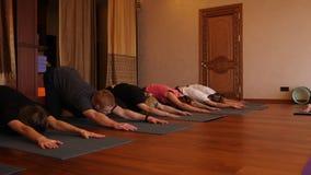 Classe di yoga di gente che esercita stile di vita sano nell'yoga dello studio di forma fisica video d archivio