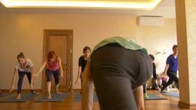 Classe di yoga di gente che esercita stile di vita sano nell'yoga dello studio di forma fisica stock footage