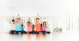 Classe di yoga nella stanza dello studio, gruppo di persone che fanno posa dell'albero con la c Fotografie Stock