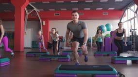 Classe do exercício da ginástica aeróbica da etapa - grupo de pessoas que exercita em steppers com o instrutor vídeos de arquivo