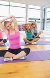 Classe ed istruttore di forma fisica che allungano le mani sulle stuoie di yoga Fotografia Stock Libera da Diritti